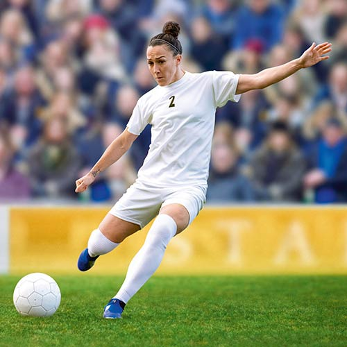 Lucy Bronze kicking a football on a field.